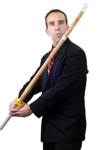 Man in business suit holding wooden sword