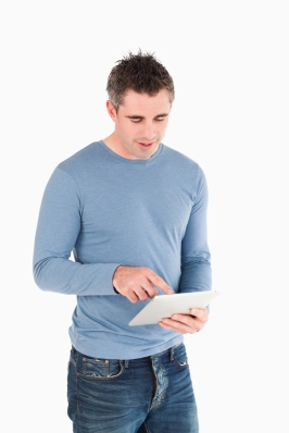 Young Man Reading Marketing Articles from Tablet